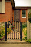 Red house facade with iron fence, green trees and flowers.  Stock Photography