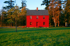 Red house in a green field. A red house in a green field under a blue sky Stock Photos