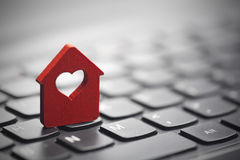 Red house with heart over laptop keyboard Stock Image