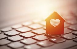 Red house with heart over laptop keyboard Stock Photos