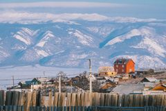 Red house on the hill of Olkhon island in Baikal lake. Red house on the hill of Olkhon island in Baikal lake with mountain range background royalty free stock photo