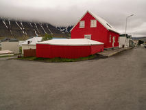 Red House Isafjordur Iceland. Bright red house on a street corner in front of a low lying cloud and fjord with streaks of snow in Isafjordur Iceland Royalty Free Stock Image