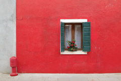 Red house with red fire hydrant outside. Royalty Free Stock Images