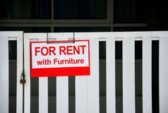 Red house for rent with furniture sign hanging on closed white fence. Copy space royalty free stock image
