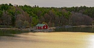 Red house on rocky shore of Ruissalo island, Finland. Red summer cabin or mokki on rocky shore of Baltic Sea. Ruissalo island, Turku archipelago, Finland Stock Photo