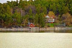 Red house on rocky shore of Ruissalo island, Finland. Red summer cabin or mokki on rocky shore of Baltic Sea at spring sunrise. Ruissalo island, Turku Stock Photo