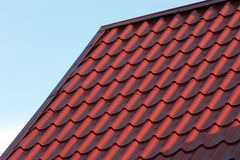 Red house roof closeup. Part of red house roof from metal tile over blue closeup Royalty Free Stock Photo