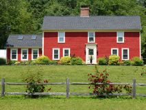 Red house rose bush. Red wooden house with rose bushes along wooden fence Stock Images