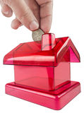 Red house shaped piggy. Red piggy-shaped house with a hand inserting a silver coin in its slot Royalty Free Stock Images