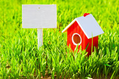 Red house and signboard on green grass Stock Photo