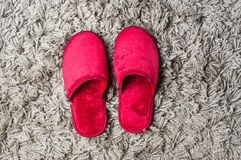 Red house slippers on gray carpet. Red house slippers on fluffy gray carpet royalty free stock images