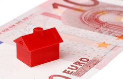 Red house on ten euro banknote. Red litle plastic house on a ten euro banknote on white background Royalty Free Stock Images
