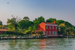 Red house by trees and water near the island of Burano, Venice stock photo