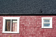 Red house with white windows a. Nd black tiled roof on a sunny day Royalty Free Stock Photography