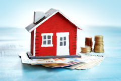 Red house on wooden background with banknotes stock image