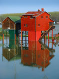 Red houses and flooding river. Two red houses on poles above flooding river Royalty Free Stock Images
