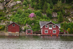 Red houses on a lake coast Stock Photos