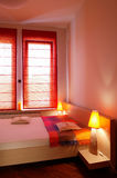 Red Hue Bedroom. Bed with side tables and window in a bedroom.  Red hue Stock Photo