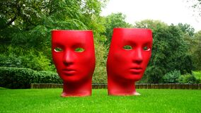 Red Human Face Monument on Green Grass Field Stock Images