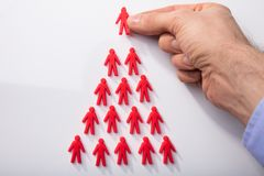 Red Human Figures Arranged In Triangular Shape. Close-up Of A Person`s Hand Arranging Red Human Figures In Triangular Shape On White Background royalty free stock photo