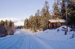 Red Hut By The Road. Red swedish wooden hut by a snow covered road surrounded by trees Stock Photography