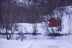 Red hut in the snowy Norwegian landscape. Facing a frozen lake royalty free stock photo