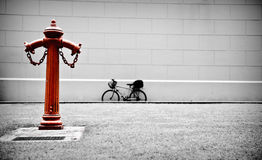 Red Hydrant. A vintage red hydrant oversee a hidden path where a bicycle is parking Stock Photos