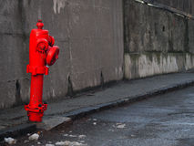 Red hydrant on gray street. A red hydrant on a street. Both the road and the background wall are very gray contrasting with the fire hydrant. Some dirt on the Royalty Free Stock Photos
