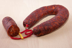 Red iberian chorizo with some cut pieces over wooden surface Royalty Free Stock Photography