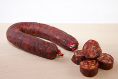 Red iberian chorizo with some cut pieces over wooden surface Royalty Free Stock Photo