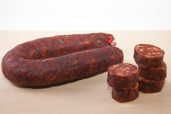 Red iberian chorizo with some cut pieces over wooden surface Stock Photography