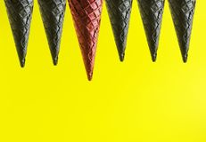 Red ice cream cone among black one as a symbol to be yourself and unique.Copy space for yor arts and text royalty free stock photography