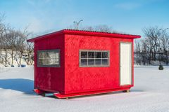 Red Ice Fishing Cabin in Ste-Rose. Ice Fishing cabins and bench and snowman in a vast spaces on the frozen Rivière des Mille Îles in Ste-Rose, Laval, Quebec Stock Photos