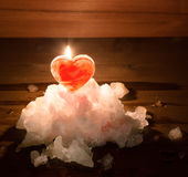 Red ice heart and the burning candle behind it on a hill of whit Royalty Free Stock Photos