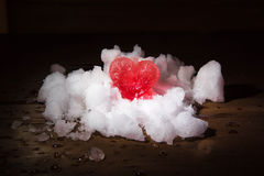 Red ice heart on the small group of snow filled on wooden boards Royalty Free Stock Image