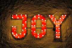 Red illuminated sign Joy. Illuminated red sign with the word JOY; fixed outside on a brick wall, lighted by bulbs and neon lights Royalty Free Stock Photos