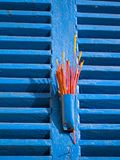 Red Incense on Blue Window Shutters. Red Incense Sticks in holder on Blue Window Shutters, Hoi An, Vietnam Stock Photography