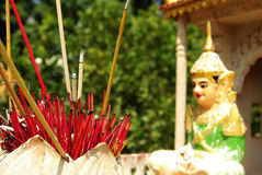 Red incense sticks in front of a buddhist statue. Many red incense sticks alight, spiritual ritual, assembled in a clay pot, in front of a buddhist figure in Stock Photography