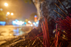 Red incense sticks in the streets at night. Long exposure with blurred lights in the background - with copyspace. With a low depth of field, background blurred Royalty Free Stock Photos