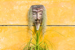 Red Indian's head sculpture on yellow wall. In garden, Thailand Royalty Free Stock Photo