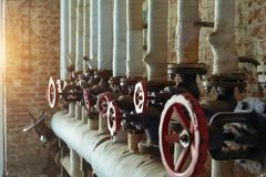 Red industrial old valves in a row on brick wall stock photo