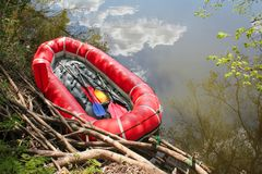 Red inflatable boat with oars raft for rafting along a  river. Against the sky reflected in the water. View from above royalty free stock photo