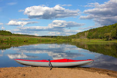 Red inflatable kayak on the sandy shore Royalty Free Stock Photography