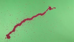 Red Ink Splatter Over Green Screen Background Stock Photo