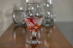 Red ink swirling in water. With other empty glasses behind on table stock photo