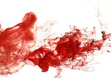 Red ink into the water. Abstract pattern falling into the water drop of red ink stock photography