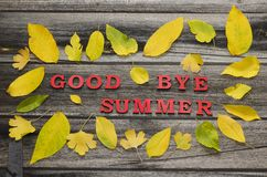 Red inscription Good bye summer on a wooden background, frame of. Yellow leaves Royalty Free Stock Photo