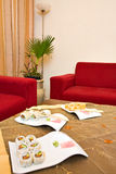 Red interior. Red living room corner with comfortable sofa and Japanese food on the table Royalty Free Stock Photos