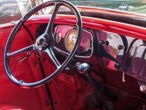 Red interior with classic car dashboard and steering wheel. View of the red interior of a classic antique car, with steering wheel and dashboard, very beautiful Stock Photography
