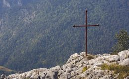 Red iron cross on top of a rock. Above a vast valley in Transylvania, Romania royalty free stock photo